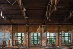 Large broken window in abandoned ruined industrial warehouse or factory building inside, ruins and demolition concept, toned