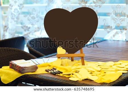 Large brown heart on the table next to the little yellow hearts for the wishes of the guests.  Writing wishing and congratulation to bride and groom  #635748695