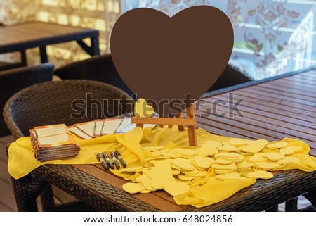 Large brown heart on the table next to the little yellow hearts for the wishes of the guests.  Writing wishing and congratulation to bride and groom  #648024856