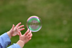Large Bubble Being Caught by a Young Child Outside in the Spring Close Up Abstract