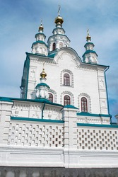 Large building of an old Orthodox church with domes against the blue sky.