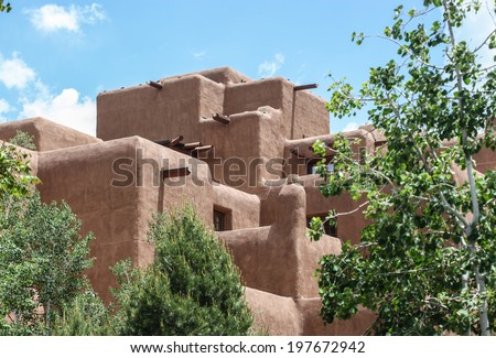 Large building with typical brown color walls and architecture in Santa Fe, New Mexico, USA/Santa Fe, New Mexico, Architectural Style/Tall and big adobe-type structure on sunny day