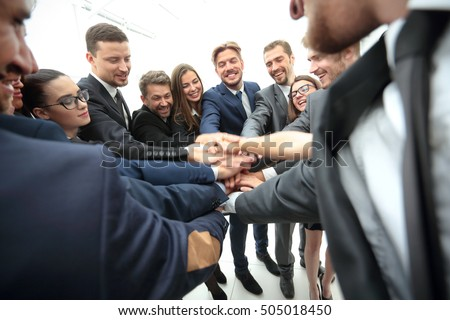 Large business team showing unity with their hands together - Shutterstock ID 505018450
