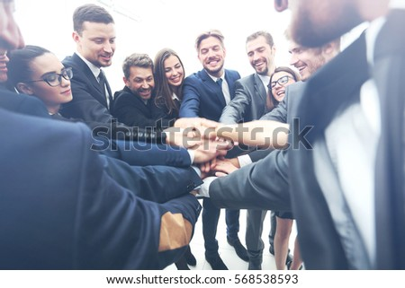 Large business team showing unity with their hands together - Shutterstock ID 568538593