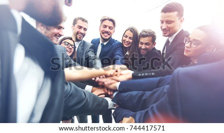 Large business team showing unity with their hands together #744417571