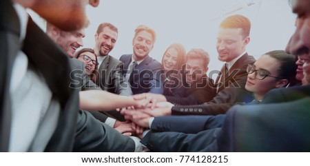 Large business team showing unity with their hands together - Shutterstock ID 774128215