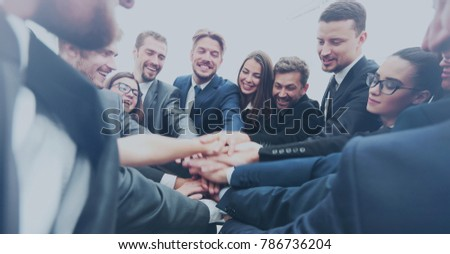 Large business team showing unity with their hands together - Shutterstock ID 786736204