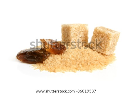 Large caramelized sugar, cane sugar cubes and sugar-sand on a white background