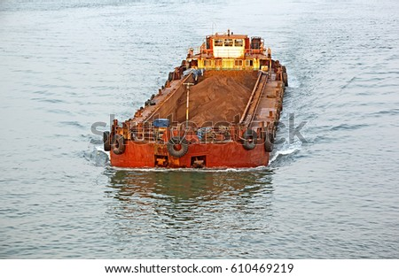 Large cargo barge transporting iron ore mined in hinterland to the main harbor for loading into big ships for exporting, along Mandovi River in Goa, India