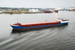 Large cargo ship leaving the port of Riga, aerial view. Terminal and fuel tanks in the background. Daugava river, Baltic sea, Latvia. Freight transportation, logistics, industry, global communications