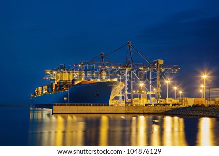 Large cargo ship on loading in the port at night.