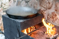 Large cauldron with freshly cooked rice. A series of the process of cooking pilaf in a huge cauldron on open fire. Frying onions and vegetables, adding meat. Appetizing pilaf cooked in a cauldron.