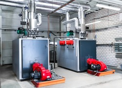 Large central heating / oil heating in a large hall, with two red fans.