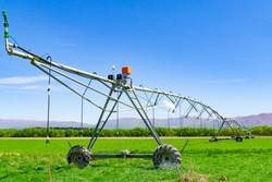 Large centre pivot irrigation system running on a farm in Canterbury, New Zealand. Long movable booms of the water distribution plant stretch across farming fields in Otago, New Zealand.