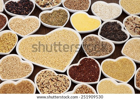 Large cereal and grain food selection in heart shaped porcelain bowls over lokta paper background. Pearl couscous in large dish. #251909530