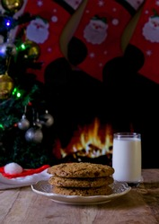 Large choc chip cookies in plate with glass of milk for Santa with fire burning in the background