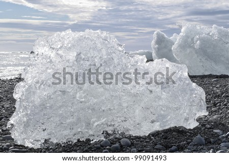 Stock Photo Large chunks of ice on a black stone beach in Iceland