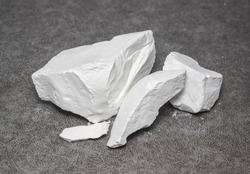 Large chunks of white food grade natural chalk on a gray background. Health care, a source of calcium, unusual food for pregnant and nursing mothers.