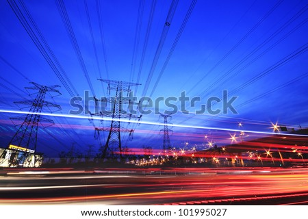 Large city road night  and transmission tower scene, long exposure night car rainbow light trails