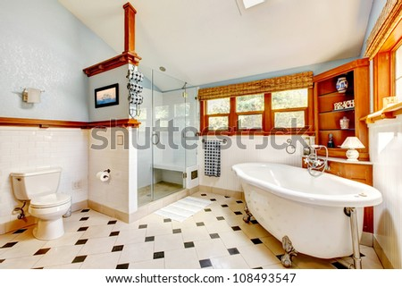 Large classic blue bathroom interior with tub and tiles and wood cabinets.