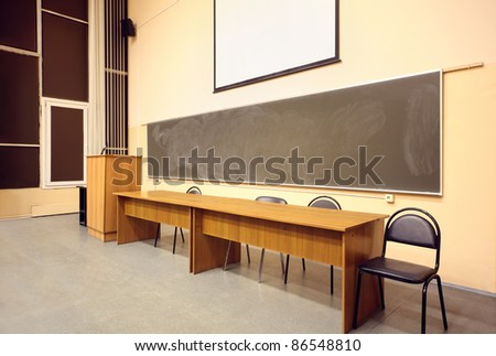 Large classroom, big blackboard, wooden table and black chairs