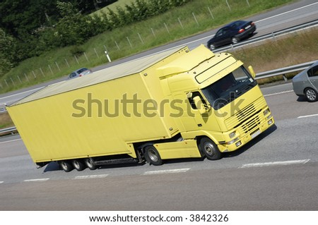 large clean yellow truck on highway surrounded by country-side