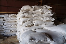 Large cloth bags with unknown bulk contents are lying in the warehouse. An image illustrating the products confiscated due to sanctions, or the capture of smugglers with illegal goods.