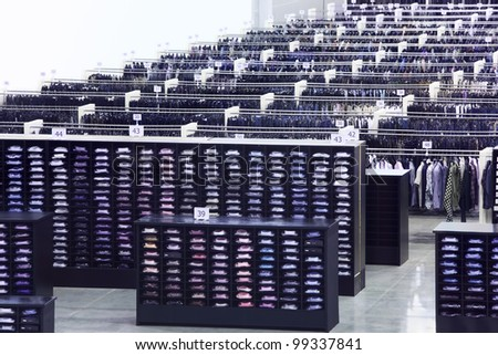 Large clothing store, many rows with hangers, shelves of shirts