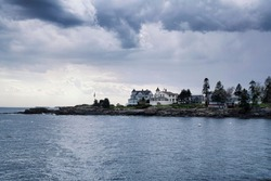 large coastal maine homes on Johns Bay in Bristol Maine under a stormy dramatic sky.