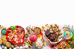 Large colorful selection of kids party food and sweets with cookies, ice cream, lollipops and candy isolated on white as a lower border with copy space