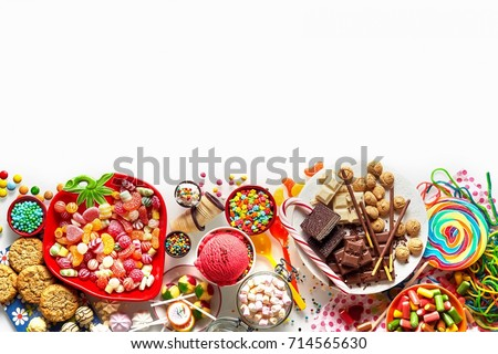 Large colorful selection of kids party food and sweets with cookies, ice cream, lollipops and candy isolated on white as a lower border with copy space #714565630