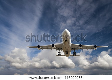 Large commercial airplane is flying in the blue sky