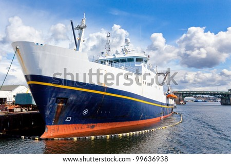 Large commercial fishing vessel docked in a ship canal