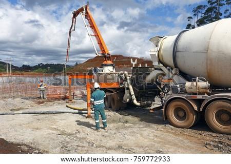 Large construction receiving concrete for foundation through a concrete mixer #759772933