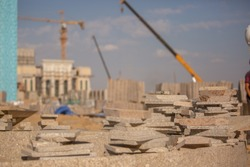 Large construction site in the city. A heap of finishing tiles lies close-up on a blurred background. Construction machinery, machinery, cranes and bulldozers operate over a large working area.