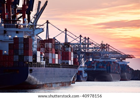 large container ships freighters in a busy port harbor during sunset