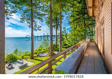 Large contemporary waterfront estate with natural woods blue sky and lush green grass in pacific northwest Stock photo ©