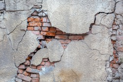Large crack on the wall of an old brick house, crumbling plaster and broken, cracked bricks. Background image