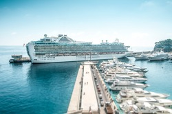 Large cruise ship in port. Luxury liner in blue water under clear sky with lots of yachts on berth in foreground. Comfortable cruise or voyage. Travelling and tourism on summer holidays and vacations.