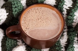 Large cup of hot chocolate on a striped knitted rug