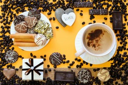 Large cup with coffee with milk and foam, chocolate chip cookies,waffles on a plate,wooden hearts,gift box, coffee beans on a yellow background