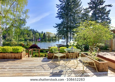 Large deck with chairs and water lake view in the spring sunny day.