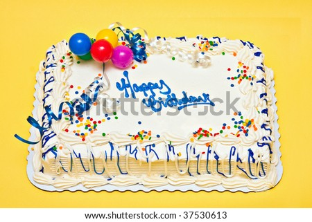 Large decorated Birthday cake with white icing, sprinkles, ribbons, balloons.