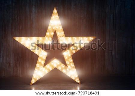Large decorative retro star with lots of burning lights on grunge concrete background. Beautiful decor, modern design element. The loft style studio. #790718491