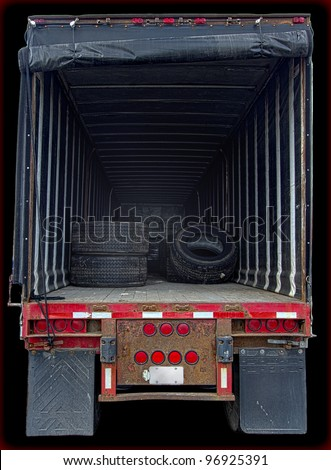 Large delivery truck interior showing nearly empty cargo space viewed from back of vehicle. Low-key lighting, vertical layout, isolated on black background, and copy space.
