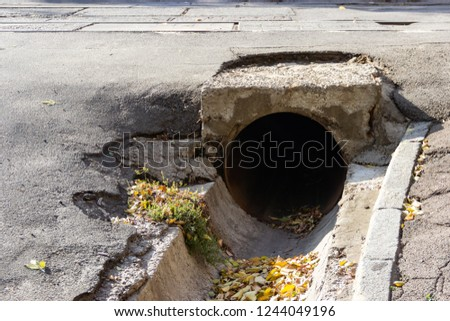 Large-diameter iron pipe under the roadway to discharge rainwater flows in the city of Dnipro, Ukraine, November 2018. Concrete gutter with autumn leaves along the roadway