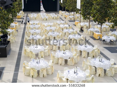 Large dining table set for wedding, dinner or another corporate event with beautiful decoration between green trees inside with people moving blurred