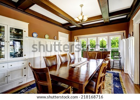 Photo of Large dining table set in brown room with white trim and coffered ceiling