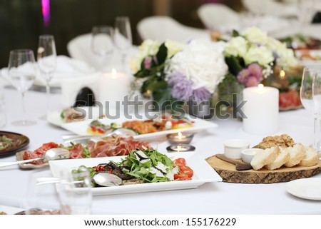 Large dining table with flowers and lots of different kinds of food at a celebration