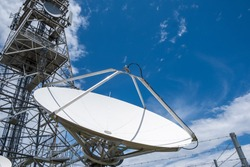 Large dish antenna against blue sky with copy space